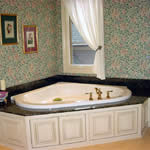 "Private Residence, Chapel Hill. This tub deck, fabricated from 2cm (3/4"") thick Verde Butterfly granite, was designed to accommodate a drop-in tub.  The splashes are usually six to eight inches in height on tubs and the plumbing fixtures can either be mounted on the stone or, sometimes"
